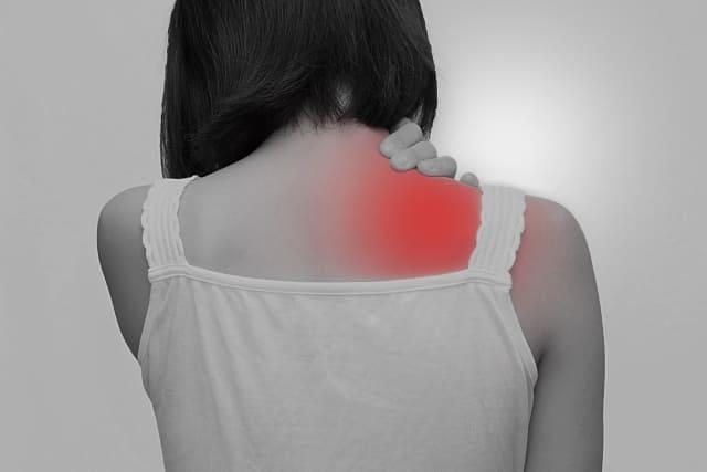 肩の痛みを我慢する女性